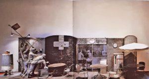 Эд Кинхольц (1927-1994, Америка). ПЕРЕНОСНОЙ ВОЕННЫЙ МЕМОРИАЛ. 1968. Гипсовое литье, надгробный камень, доска, флаг, плакат, ресторанная мебель, мусорный ящик, фотография, действующий автомат по продаже еды, чучело собаки, собачий поводок, дерево, металл, стекловолокно, мел, веревка. 268х274,3х220,9 см. Людвиг музеум, Кёльн (Германия). Инсталляция